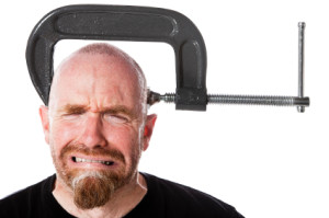 Man grimaces in pain and sweats as a clamp squeezes his head. Camera: Canon EOS 1Ds Mark III.
